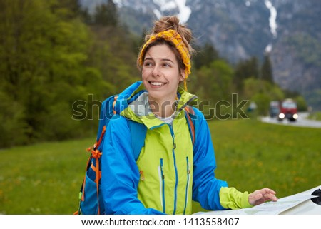 Dreamy cheerful woman dressed in active wear, uses tourist map for finding right route, wears backpack, focused aside with glad expression, breathes fresh air in mountains, stands on green grass #1413558407