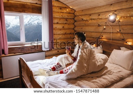 Dreamy Christmas vacation in log house with winter mountains landscape in window. Young guy wearing traditional pajamas looking at window while relaxing in bed inside cozy cabin. #1547871488