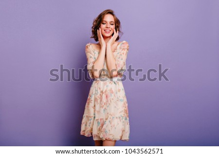 Dreamy cute girl with trendy makeup gently touching her face, posing on purple background. Shy young lady in dress standing with eyes closed with romantic smile.
