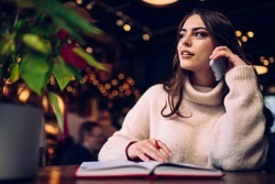Dreamy female in casual sweater speaking on phone while sitting with notepad and pen at cozy illuminated cafe and looking away