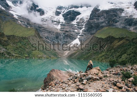 Dreamy female tourist sitting on stone on rock of high hill and admiring beauty of environment during wanderlust in Salkantay.Young man traveller resting during hiking trek enjoying mountains