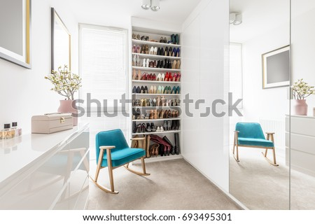 Dreamy feminine wardrobe with white furniture, big mirror, shoe closet, beige carpet, blue retro armchair and pastel pink accessories
