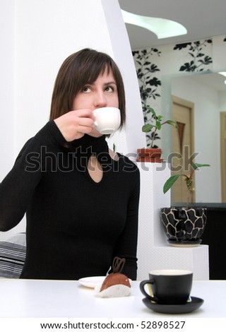 Dreamy girl drinking coffee in a cafe