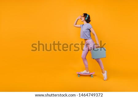 Dreamy girl in pink pants standing on skateboard and listening music. Inspired curly female model in headphones posing with blue valise.