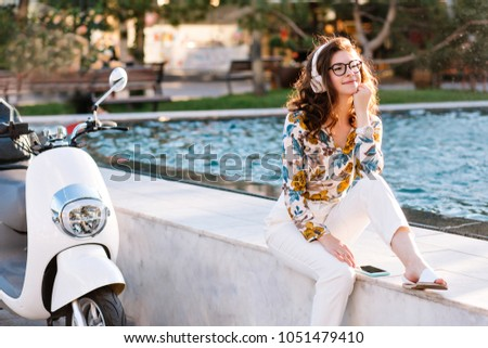 Dreamy girl with elegant hairstyle listening music and looking away, spending time near fountain. Amazing young lady in glasses and big white earphones chilling outdoor after riding on scooter. #1051479410