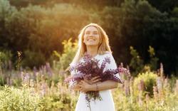Dreamy girl with short blond hair holding a bouquet of lupines in hes hands.