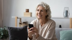 Dreamy happy hoary mature elderly woman holding smartphone, feeling positive about received message. Smiling pleasant middle aged grandma looking outside, thinking of future meeting or dating at home.