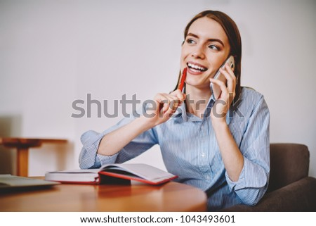 Dreamy hipster girl thining about offer of new startup project during phone conversation with friend on smartphone device sitting at notebook in coworking space near publicity area for advertising