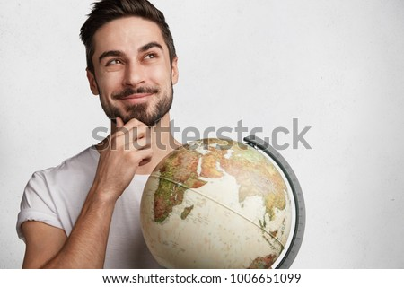 Dreamy hipster guy with globe thinks about which new country to visit, being in good mood as has vacations, isolated over white background. Shot of handsome male tourist. World wide concept.