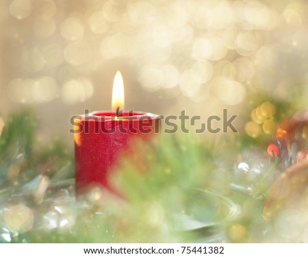 Dreamy image of a Christmas candle burning in the middle of a wreath - stock photo