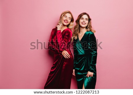 Dreamy ladies in stylish velvet dresses posing with cute smile. Indoor photo of attractive white girls isolated on rosy background.