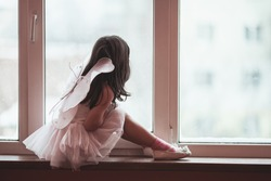 Dreamy little girl in a pink tutu dancing looks out the window