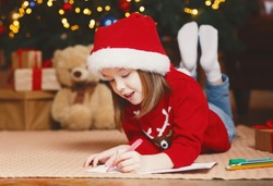 Dreamy little girl in red xmas hat writing letter to Santa under xmas tree, making wishes on Christmas Eve, free space