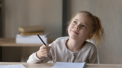 Dreamy little girl sit at desk studying look in distance visualizing or thinking, small child dreamer feel unmotivated distracted from preparing doing homework at home, lost in dreams or imagination