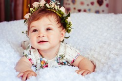Dreamy little girl with rose wreath on golden hair lies on fluffy blanket