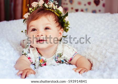 Dreamy little girl with rose wreath on golden hair lies on fluffy blanket #593914841