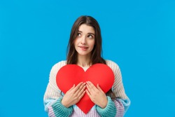 Dreamy lovely and shy, thoughtful attractive woman want give valentines day heart cardboard to express sympathy, confess love and affection, dreamy looking up, biting lip tempting, blue background