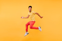 Dreamy male model. Indoor shot of african guy in bright clothes jumping on yellow background.