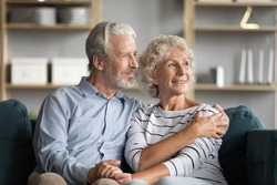 Dreamy middle aged senior loving retired family couple looking in distance, planning common future or recollecting memories, enjoying peaceful moment relaxing together on cozy sofa in living room.