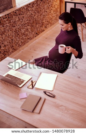 Dreamy mood. Kind woman keeping smile on her face while feeling movements in belly #1480078928