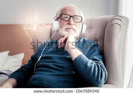 Dreamy mood. Thoughtful nice senior man listening to music and smiling while being in a dreamy mood #1067089340