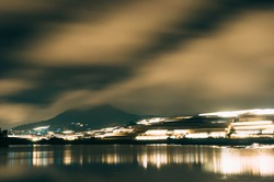 Dreamy nature scenery of fog covered mountains, orange sky, illuminated greenhouses at the bank of the lake and the glowing reflections. Long-exposure landscape of Dalat, Vietnam at night.