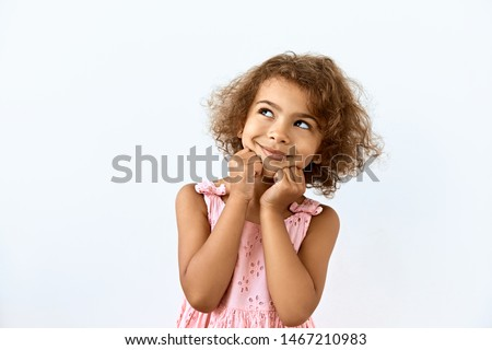 Dreamy,pleased, thinking emotion . Wish concept. Little African American girl face portrait on white backgound.