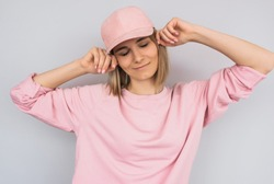 Dreamy pretty Caucasian blonde young female wearing pink sweater, enjoy with closed eyes with pink cap on head, isolated on white studio background. Positive people emotion concept.