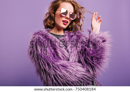 Dreamy pretty girl plays with short curly hair standing on bright background. Indoor portrait of pensive female model in sunglasses and purple fluffy coat.