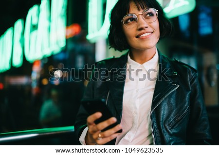Dreamy pretty young woman in eyewear smiling while walking with smartphone in urban setting of night city with neon lights. Fashionable cheerful hipster blogger in stylish wear and cellular in hand