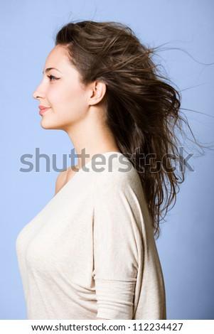Dreamy profile portrait of gorgeous young brunette woman.