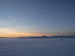 Dreamy, scenic winter sea landscape at sunset, Oslofjorden is covered with ice and snow and allows people to
