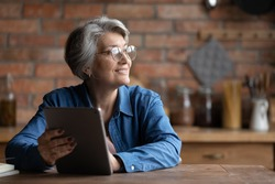 Dreamy senior grey haired woman in spectacles holding digital computer tablet in hands, looking in distance, copy space for advertising text of retired old people and modern technology easy usage.