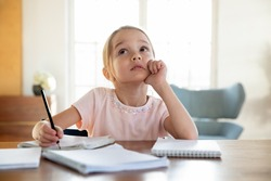 Dreamy small Caucasian girl child sit at desk feel unmotivated doing home task assignment alone. Thoughtful little kid look in distance dreaming thinking, lazy preparing homework. Learning concept.