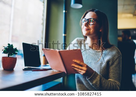 Dreamy smart female reader pondering on interesting plot in textbook.Smiling young woman with notepad in hands thinking on future plans sitting in coffee shop.Thoughtful pretty student with book #1085827415