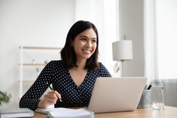 Dreamy smiling Asian businesswoman sitting at desk with laptop, happy woman looking to aside, dreaming about good future or new opportunities, pondering strategy, planning project, home office