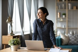 Dreamy smiling young indian woman student online teacher freelancer looking away dreaming about professional future success hope for new opportunity concept at home office stand at table with laptop