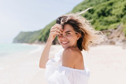 Dreamy tanned woman looking over shoulder while standing at sea coast. Adorable blonde girl posing with pleasure at tropical island in hot day.