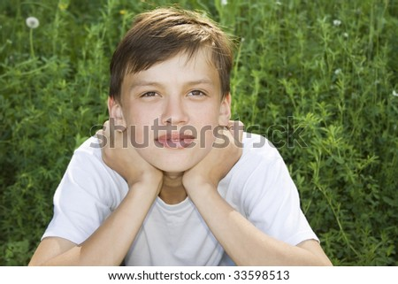 Dreamy teenager is relaxing, and he sit on the grass