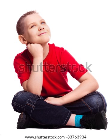 dreamy ten year old boy sitting on the floor, isolated against white