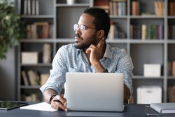 Dreamy thoughtful African American businessman looking to aside, sitting at work desk with laptop, serious man pondering project plan or strategy, making difficult decision, solving problem