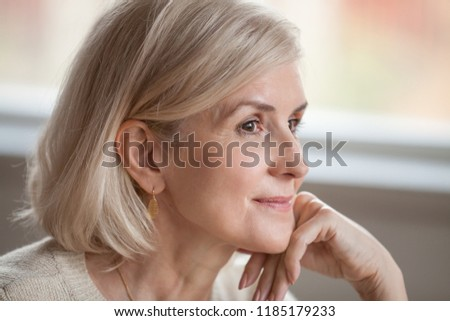 Dreamy thoughtful mature attractive woman relaxing hoping thinking of happy future, smiling senior middle aged lady looking away realizing positive thoughts feeling optimistic in good expectation