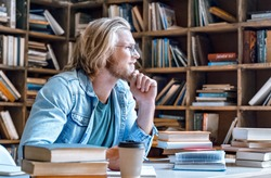 Dreamy thoughtful young teacher man male student hipster author glasses chin on hand study in library sit at desk write essay ready for exam do homework assignment smile look away education concept.