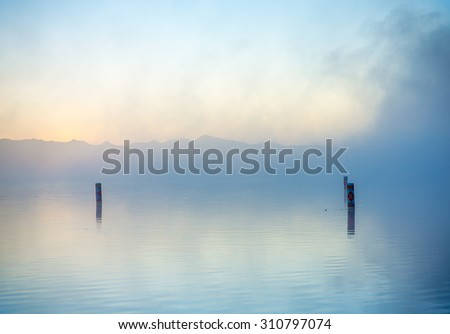 Dreamy water scenery with morning mist over calm surface