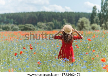 Dreamy woman in red dress and hat in beautiful herb flowering poppy field. Vintage elegant romantic look. concept of lovely summer.