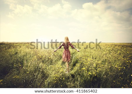 dreamy woman walking in nature towards the sun