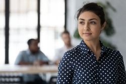 Dreamy young Indian female employee look in distance thinking or pondering, thoughtful happy millennial biracial woman worker plan consider future career opportunities, business vision concept