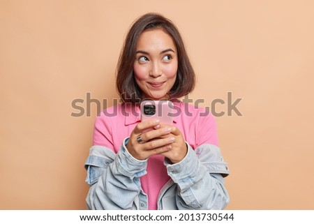 Dreamy young pretty Asian woman with dark hair holds mobile phone has thoughtful expression thinks about received message wears pink t shirt denim jacket looks away isolated over beige background.