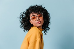 Dreamy young woman in sunglasses looking at camera. Front view of interested curly girl isolated on blue background.