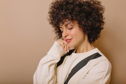 Dreamy young woman in with short afro haired is looking down. Front view of interested curly girl isolated on beige background. High quality photo